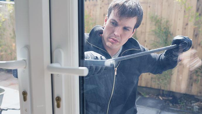 Un okupa forzando la cerradura de una casa